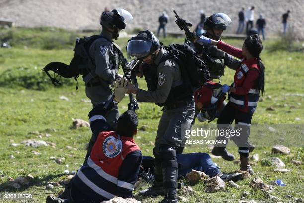 TOPSHOT Palestinian Civil Defence volunteers scuffle on March 12 2018 in the West Bank town of Birzeit near Ramallah with Israeli soldiers as they...