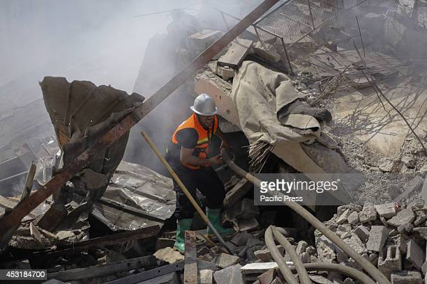 Palestinian civil defence worker tries to extinguish a fire broke out in one of the houses east of Beit Hanoun after being targeted by the Israeli...