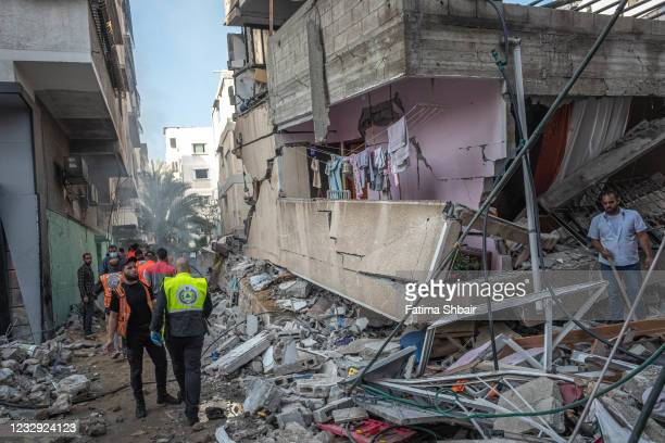 Palestinian civil defense men search for people in the rubble of a destroyed building after an Israeli air strike in Gaza City on May 16, 2021 in...