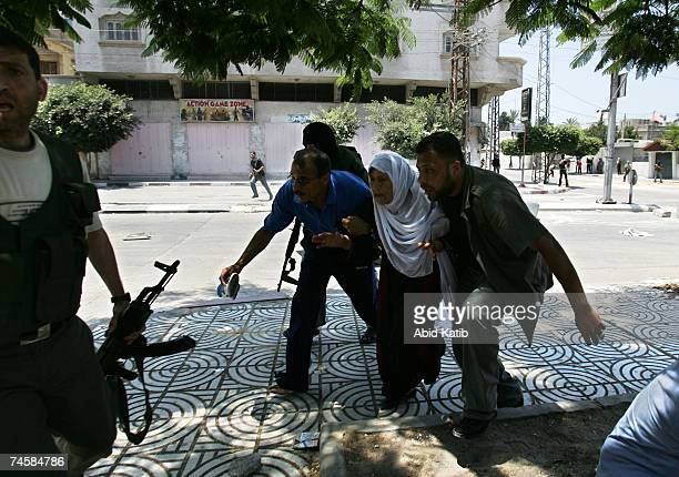 Palestinian civilian men and an elderly woman run to take take cover during a clash between Fatah militants and militants of the Hamas movement on...