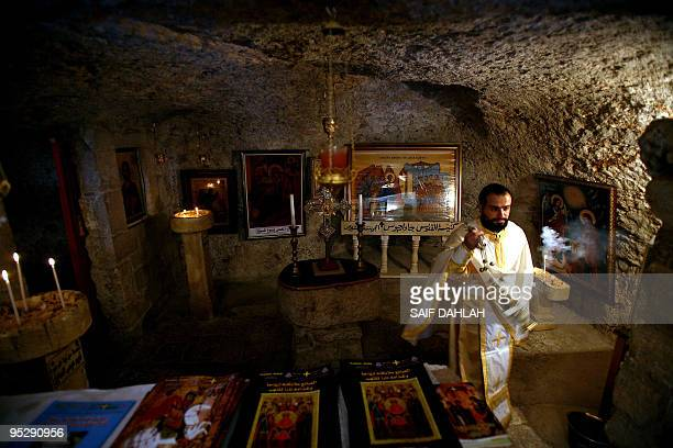 A Palestinian clergyman swings an incense burner during a Christmas mass at the Saint George Orthodox Church in the West Bank village of Burqin near...