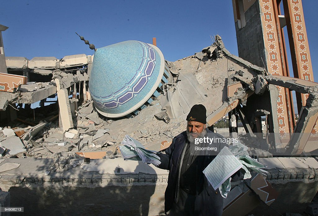A Palestinian collects pages of a Koran from the rubble of t : News Photo