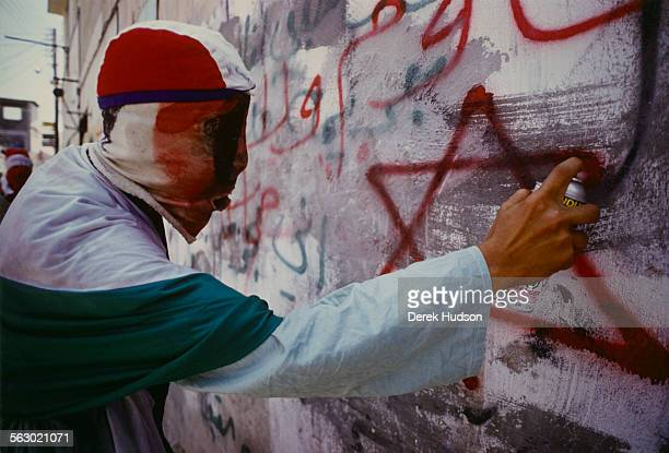 Palestinian combatants wearing disguises mark a wall with antiIsraeli graffiti occupied Palestinian territories June 1989