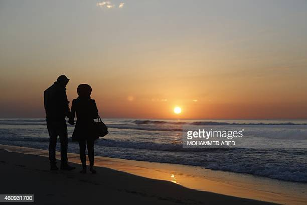 A Palestinian couple walk down the beach during the last sunset of 2014 off the coast of Gaza City on December 31 2014 AFP PHOTO / MOHAMMED ABED