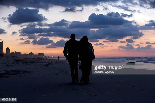 Palestinian couple walks during sunset at the Gaza beach in Gaza City Gaza on December 31 2016