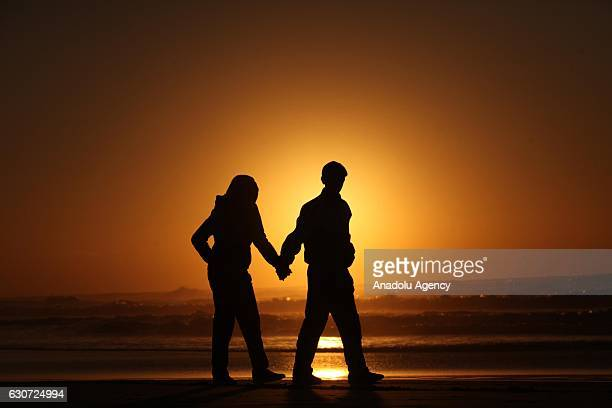 Palestinian couple walks during sunset at the Gaza beach on December 31 2016 in Gaza City Gaza