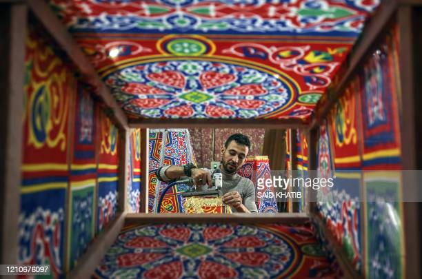 """Palestinian craftsman fashions a traditional """"fanous"""" lantern, a decoration used to celebrate the start of the Muslim holy month of Ramadan beginning..."""