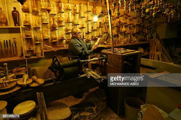 Palestinian craftsman Hesham Kuhail carves decorative wooden objects at his workshop in Gaza City on January 23 2017 / AFP / MOHAMMED ABED