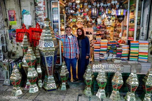 Palestinian craftsman Issam Zughair stands with his wife next to an assortment of Ramadan lanterns in the entrance of his shop in the old city of...