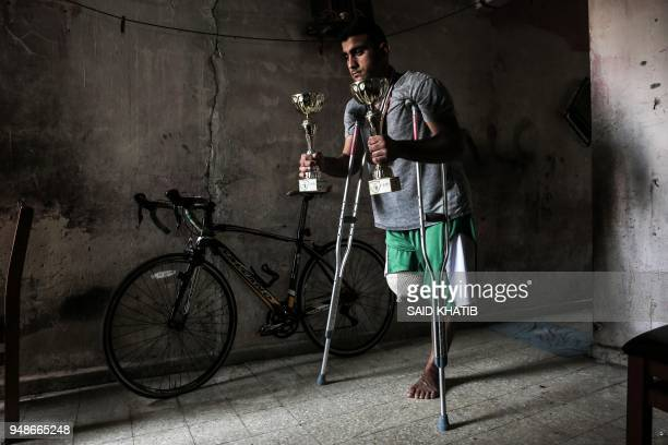 TOPSHOT Palestinian cyclist Alaa AlDaly who lost his leg by a bullet fired by Israeli troops along the Gaza border during a protest stands next to...