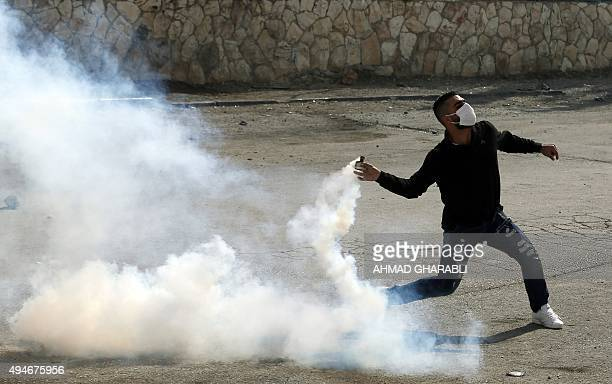 A Palestinian demonstrater throws back a tear gas canister towards Israeli security forces during clashes near the Israeli controvertial separation...