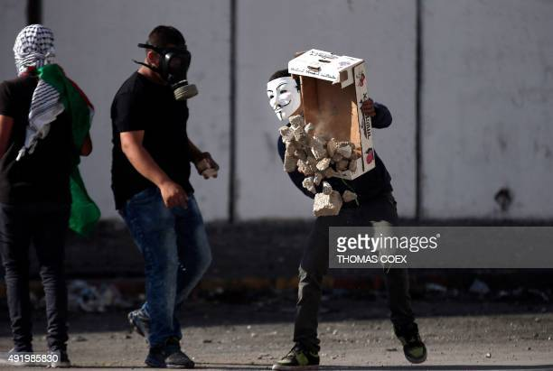 Palestinian demonstraters gather a pile of stones to throw towards Israeli security forces during clashes in the Palestinian neighbourhood of Shuafat...