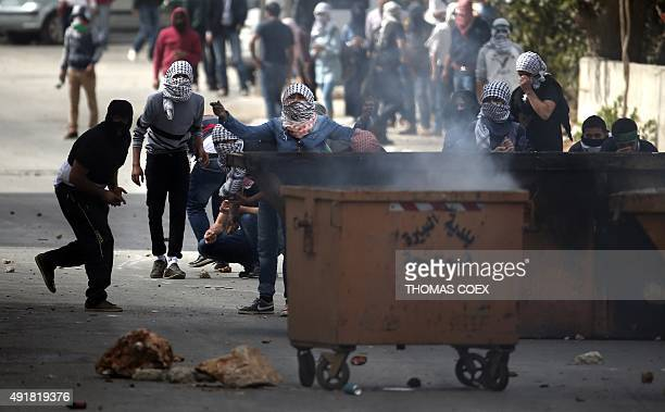 Palestinian demonstraters throw stones towards Israeli security forces during clashes in Beit El near the West Bank city of Ramallah on October 8...