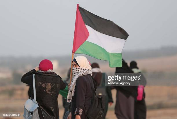 Palestinian demonstrator carries a flag during a Great March of Return demonstration near Al Bureij Refugee Camp on the GazaIsrael border in Gaza...