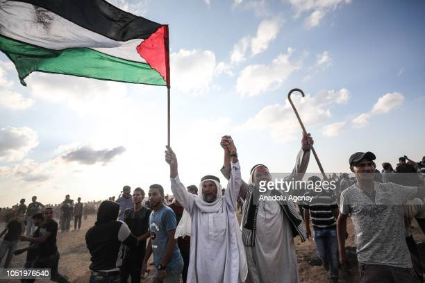 "Palestinian demonstrator carries a Palestinian flag during the ""Great March of Return"" demonstration near Israel-Gaza border, in Khan Yunis, Gaza on..."