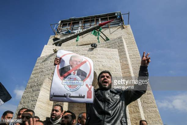 Palestinian demonstrator chants slogans as while holding a poster of US President Donald Trump, during a protest against his expected announcement of...