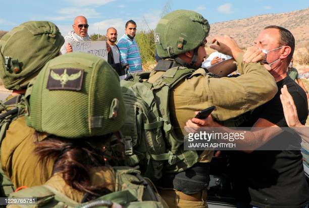 A Palestinian demonstrator clashes with Israeli soldiers during a protest against Jewish settlements on November 24 in the Jordan Valley in the...