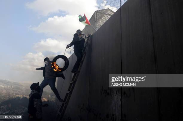 TOPSHOT Palestinian demonstrator climbs a ladder with a flaming tyre by Israeli's controversial separation barrier in the occupied West Bank village...