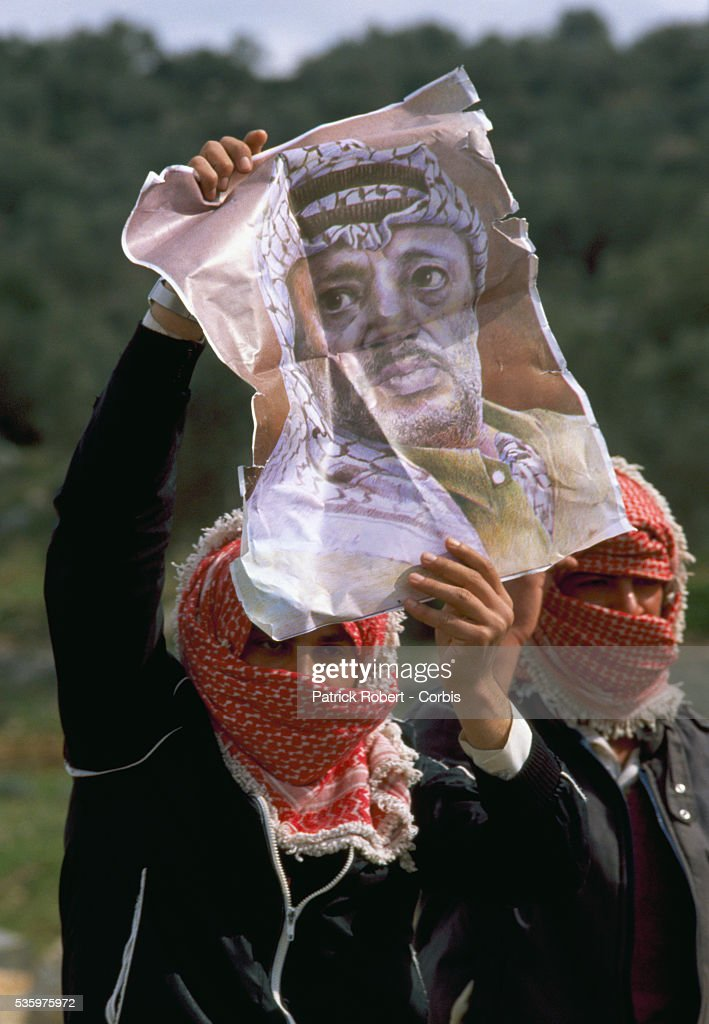 A Palestinian demonstrator displays a poster of Palestinian Liberation Organization leader Yasser Arafat during an uprising in Ramallah. Violence broke out after rebel Israeli and Palestinian fighters protested in the disputed territory of West Bank during the first Intifada.