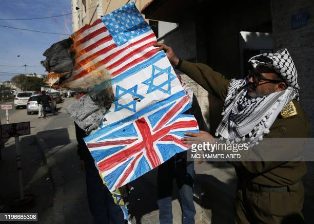 A Palestinian demonstrator dressed up like the late leader Yasser Arafat burns along with other protesters drawings representing the flags of Israel...