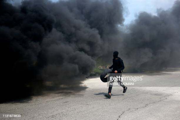 Palestinian demonstrator from Birzeit University carries a tyre to burn during clashes with Israeli forces in Ramallah near the Jewish settlement of...