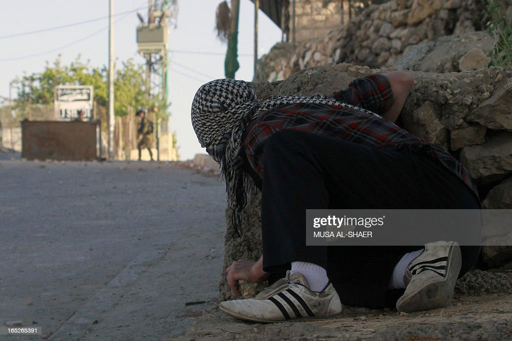 A Palestinian demonstrator hides behind a wall during clashes in al-khader village near the West Bank town of Bethlehem following the death of a Palestinian prisoner on April 2, 2013. The Palestinian leadership blamed Israel for the death of Maisara Abu Hamdiyeh, a long-term prisoner with cancer, hiking tensions over a tinderbox issue closely followed on the Palestinian street.