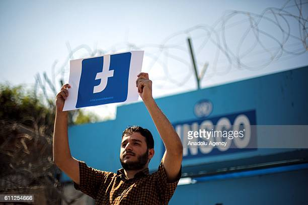 Palestinian demonstrator holds a banner during a protest against blocking of Facebook to Palestinian's accounts in front of the Office of United...