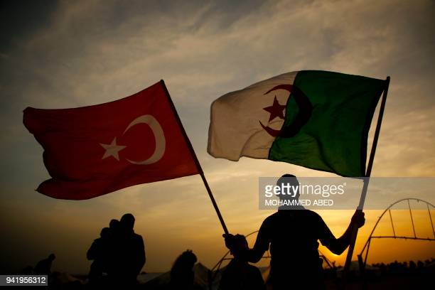 A Palestinian demonstrator holds the Turkish and Algerian national flag at the border between Gaza and Israel during clashes with Israeli forces east...