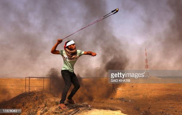 Palestinian demonstrator hurls rocks with a slingshot next to burning tyres during a protest by the border with Israel, east of Rafah in the southern...