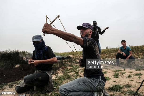 Palestinian demonstrator hurls stones at Israeli troops during clashes near Khan Yunis by the border fence between Israel and the southern Gaza Strip...