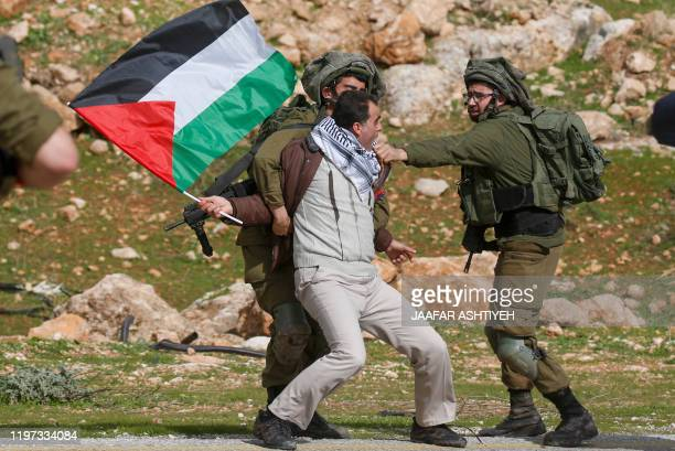 Palestinian demonstrator is detained by Israeli soldiers during a protest near the West Bank village of Tubas, near the Jordan Valley, on January 29...