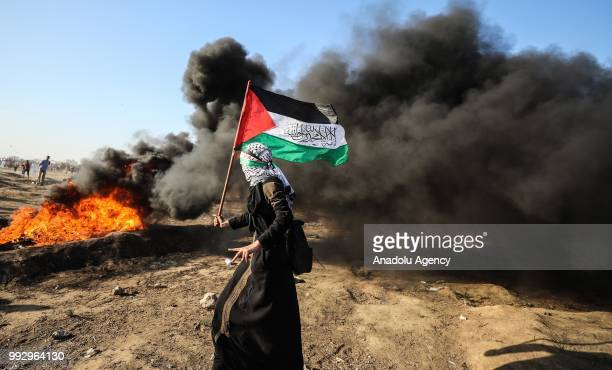 Palestinian demonstrator is seen as other demonstrators burn tires in response to Israeli security forces' intervention during a demonstration held...