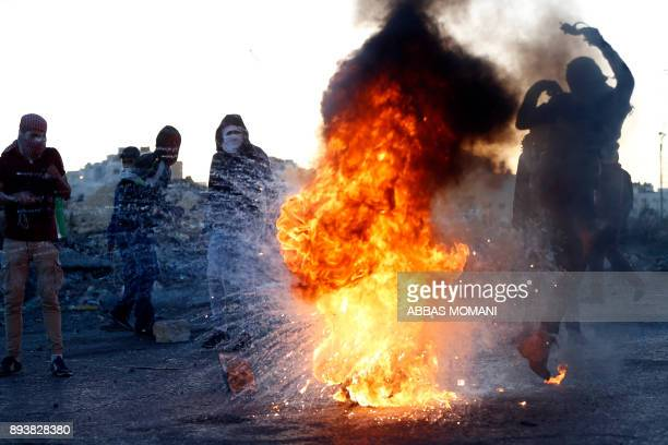 Palestinian demonstrator kicks a burning tire during clashes with Israeli forces near an Israeli checkpoint in the West Bank city of Ramallah on...