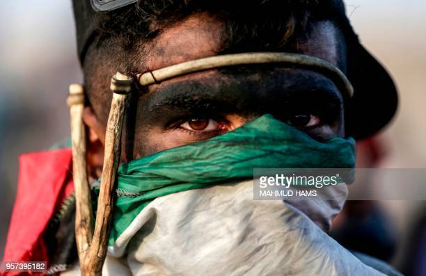 Palestinian demonstrator looks on during clashes with Israeli forces along the border with the Gaza strip east of Gaza City on May 11 as Palestinians...