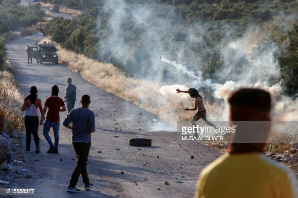 A Palestinian demonstrator returns a tear gas canister during clashes with Israeli soldiers in the town of Tuqua in the Israelioccupied West Bank on...