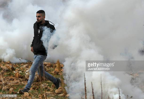 A Palestinian demonstrator runs for cover during clashes with Israeli soldiers during a protest against Jewish settlements on November 24 in the...