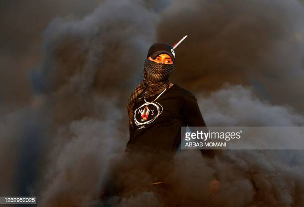 Palestinian demonstrator stands amidst smoke from burn tires during a protest against the tension in Jerusalem and the Israeli-Gaza fighting, on May...