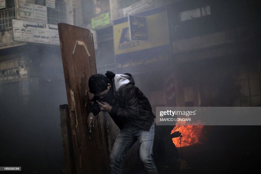 A Palestinian demonstrator stands behind a barricade during clashes with Israeli security forces in the West Bank city of Hebron on April 4, 2013. Clashes rocked the West Bank as thousands attended the funerals of a prisoner and two teenagers shot dead by Israeli troops and Palestinian president Mahmud Abbas said the killings jeopardised US efforts to rekindle peace talks.
