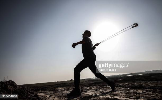 Palestinian demonstrator swings a slingshot during clashes with Israeli forces near the border with Israel in the southern Gaza strip city of Khan...