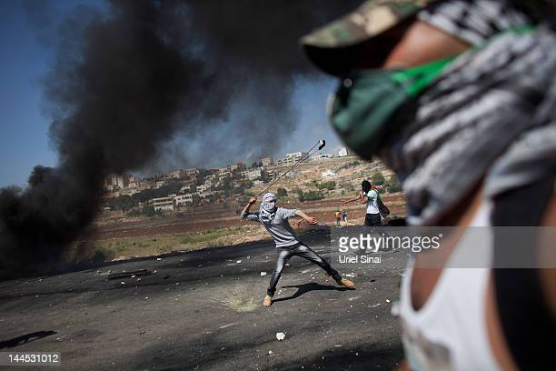 A Palestinian demonstrator throws a stone toward Israeli soldiers during clashes outside of Ofer Prison on May 15 2012 near the West Bank city of...