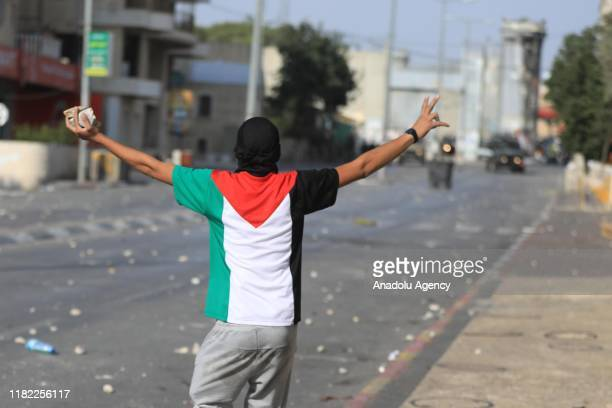 Palestinian demonstrator throws rocks in response to Israeli soldiers' intervention during a demonstration to protest against Israeli attacks towards...