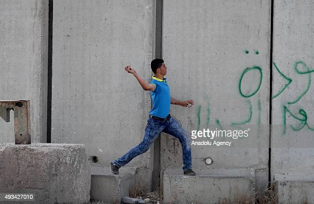 Palestinian demonstrator throws stones at Israeli soldiers during a protest against Israeli violations in Tulkarm West Bank on October 20 2015