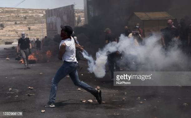 Palestinian demonstrator throws teargas canisters back at Israeli forces during clashes near the Jewish settlement of Beit El near Ramallah, West...