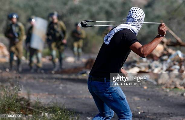 Palestinian demonstrator uses a slingshot to hurl stones toward Israeli security forces during clashes with them following a weekly demonstration in...