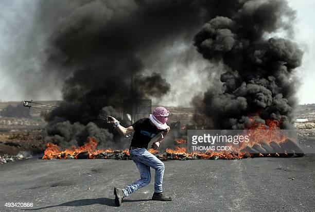A Palestinian demonstrator uses a slingshot to throw stones towards Israeli security forces from behind burning tires during clashes in the West Bank...
