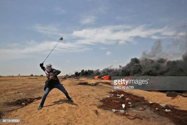 Palestinian demonstrator uses a slingshot to throw stones towards Israeli security forces near the southern Gaza Strip town of Khan Yunis during the...
