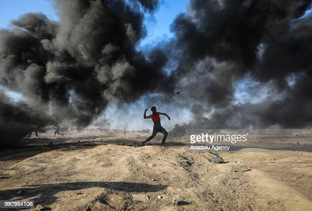 Palestinian demonstrator uses slingshots to throw rocks and burns tires in response to Israeli security forces' intervention during a demonstration...