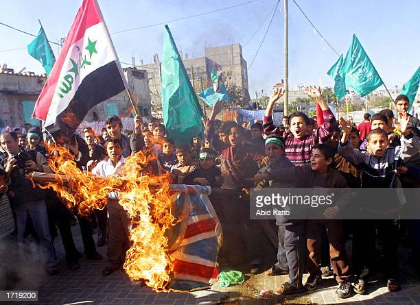 Palestinian demonstrator waves an Iraqi flag as a British flags burns during a rally January 10, 2003 in the Jabaliya refugee camp, Gaza Strip. About...