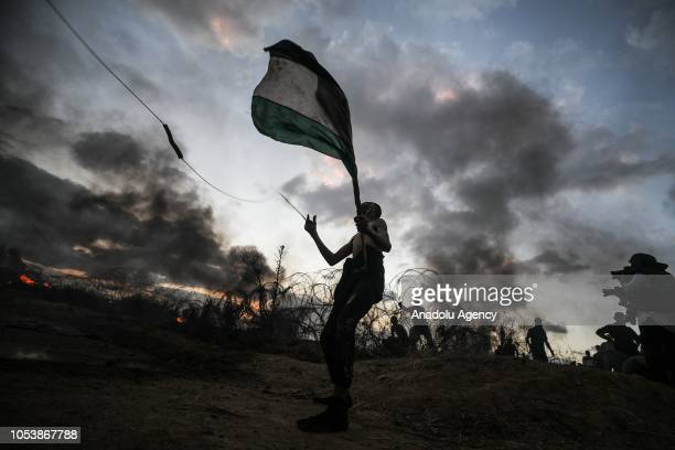 "Palestinian demonstrator waves Palestinian flag during the ""Great March of Return"" demonstration on the Israel-Gaza border near Malka in Gaza City,..."