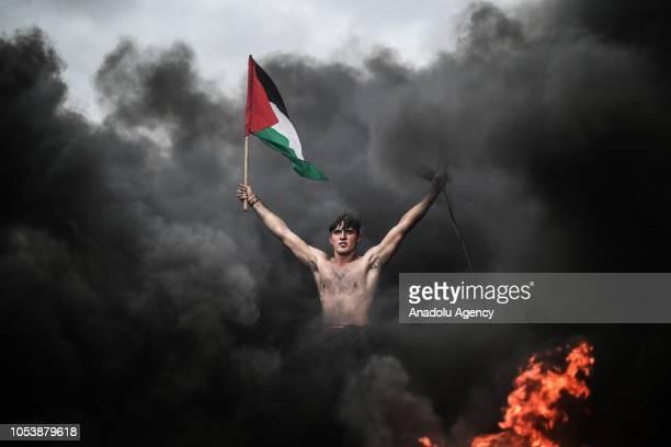 Palestinian demonstrator waves Palestinian flag during the Great March of Return demonstration on the IsraelGaza border near Malka in Gaza City Gaza...